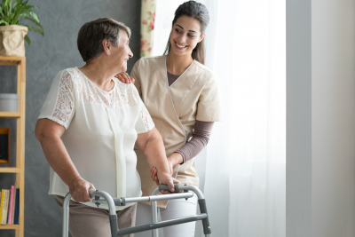 caregiver assisting the senior woman to walk