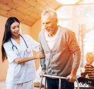 nurse assisting the senior man to walk