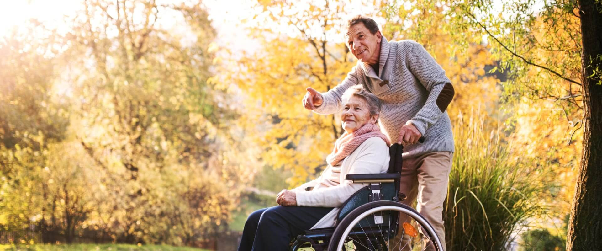 old woman on a wheelchair and a senior man assisting her