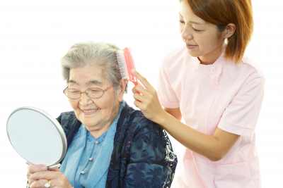 caregiver brushing the hair of the senior woman