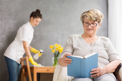 caregiver cleaning the house while senior woman is reading a book